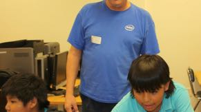 Chandler volunteer Don Wilde spends his spare time promoting FIRST Lego© League Robotics competitions. Don recruits and trains team mentors from Intel and helps start new teams across the state. Here he's helping a student from the Salt River Pima Indian Community program his robot.