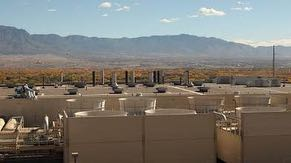 Rooftop view from Fab 11X overlooking central utility building, cooling towers, Rio Grande Valley, Albuquerque and Sandia & Monzano Mountains.