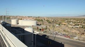 Rooftop view from central utility building of two 1-million gallon water tanks, 250,000 gallon fire system water tank, oil-free air tank, emergency generator exhaust stack, the Village of Corrales and North Valley.